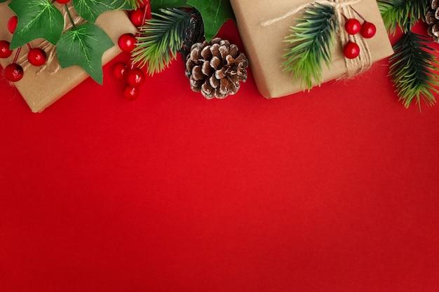 Maretak, dennenappels en kerstcadeaus op rode tafel