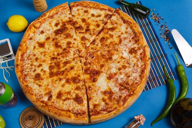 Margarita pizza met basilicum op een blauwe achtergrond bovenaanzicht zelfgemaakte vegetarische pizza met kaas