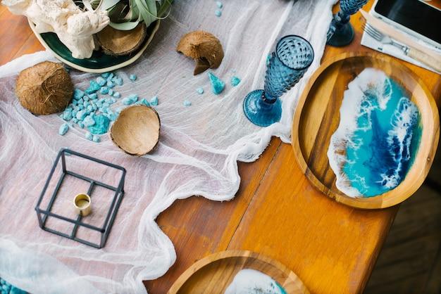 Marien decor op een feestelijke houten tafel met kokosnoot en blauwe glazen