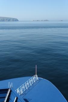 Mariene achtergrond met scheepsdek en uitzicht op zee in blauwe monochrome kleur en kopieerruimte