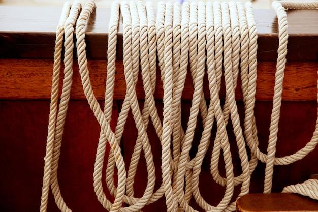 Mariene kabels op een rij op uitstekende houten boot