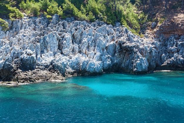 Mariene wandeling op een piratenschip turkije, beboste berg die boven de smaragdgroene zee uitsteekt