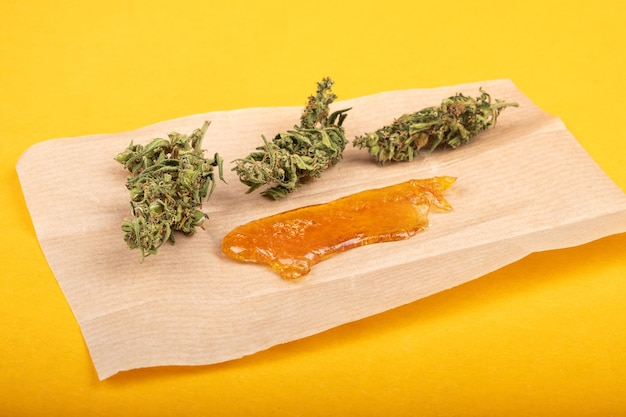 Marihuanaknop en sterk extract van gouden cannabiswas met hoge thc close-up