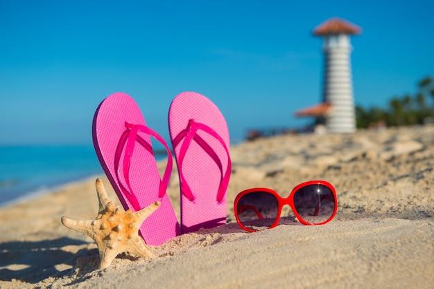 Marine accessoires voor dames: sandalen, zonnebrillen en zeester op tropisch zandstrand tegen de achtergrond van vuurtoren