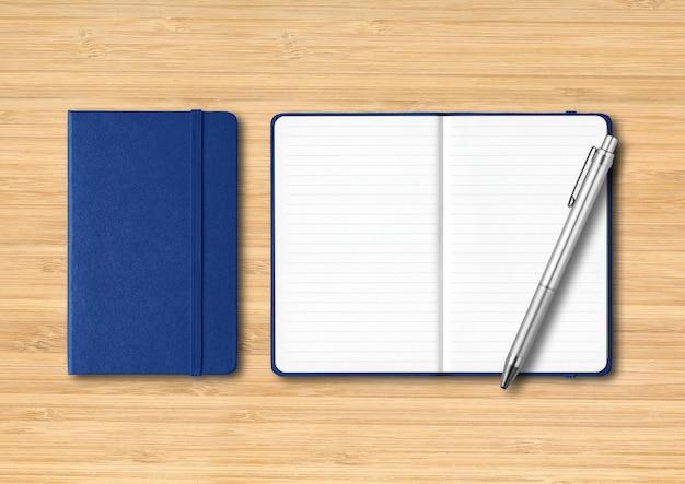 Marine blauwe gesloten en open gelijnde notitieboekjes met een pen. mockup geïsoleerd op houten achtergrond