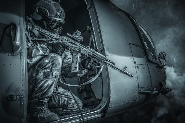 Marine richt zich op een richtkijker vanuit een vliegende helikopter. het concept van militaire conflicten. gemengde media