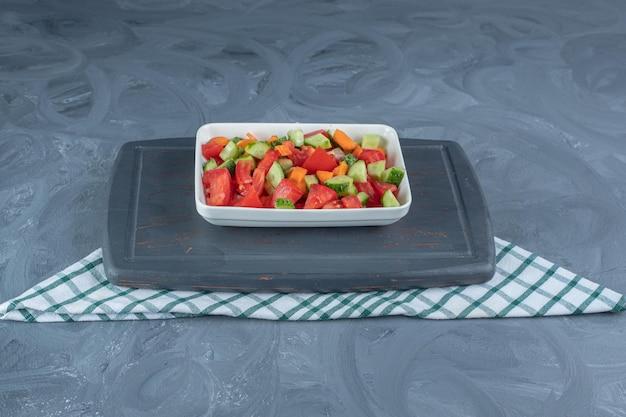 Marineblad onder een schaal met herderssalade gemengd met plakjes wortel op marmeren tafel.