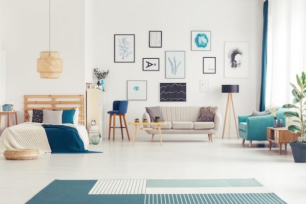 Marineblauw woonkamerinterieur met banken, postercollectie en kingsize bed