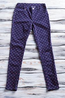 Marineblauwe broek met stippen donkere broek op houten achtergrond kwaliteit katoenen broek voor meisjes stijlvol ontwerp o...