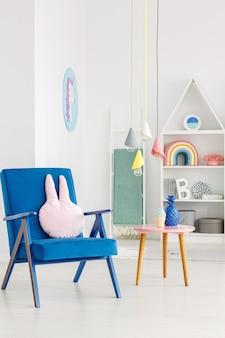 Marineblauwe fauteuil met een konijnenkussen naast een tafel en witte planken op de achtergrond in een kinderkamerinterieur