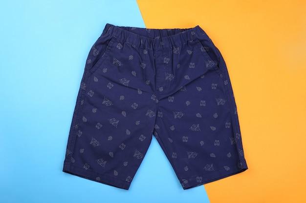 Marineblauwe heren casual korte broek op blauwe en oranje pastelkleurachtergrond