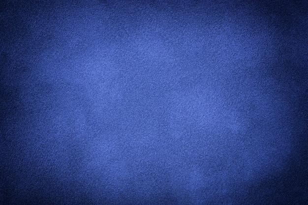 Marineblauwe matte achtergrond van suède stof met vignet, close-up. fluwelen textuur van naadloze indigo textiel met kleurovergang, macro.