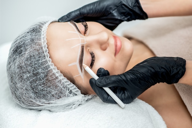 Markering op wenkbrauwen van jonge vrouw met potlood tijdens permanente make-up.