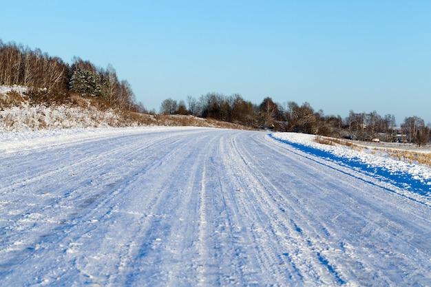 Markeringen van een auto achtergelaten in de sneeuw na een passerende auto, winterseizoen, een diepe laag sneeuw na een sneeuwval, close-up