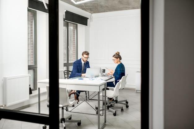 Marketeer of analyc-managerteam gekleed in pakken werkend met papieren kaarten en laptops in het witte kantoorinterieur