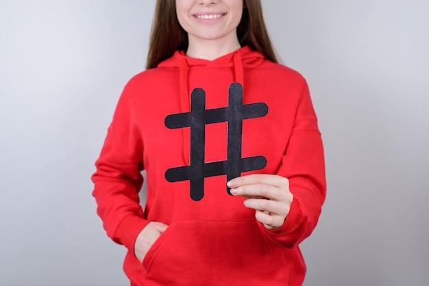 Marketing jongerenwebsite tweet digitaal verkoopconcept. bijgesneden close-up foto van vrolijke positieve blij optimistische toothy glimlach jongere met grote grote zwarte hashtag in palm geïsoleerde grijze achtergrond
