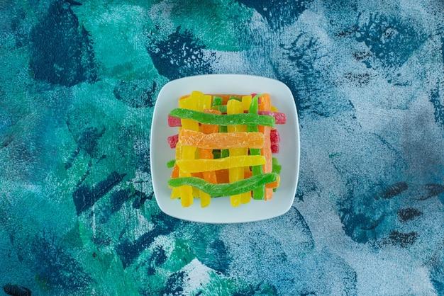 Marmelade in de vorm van gekleurde stokjes in een schotel, op de marmeren tafel.