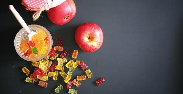 Marmelade in een vaas op tafel. snoepjes in een kom op een zwarte achtergrond. veelkleurige gelei-snoepjes voor kinderen. Premium Foto
