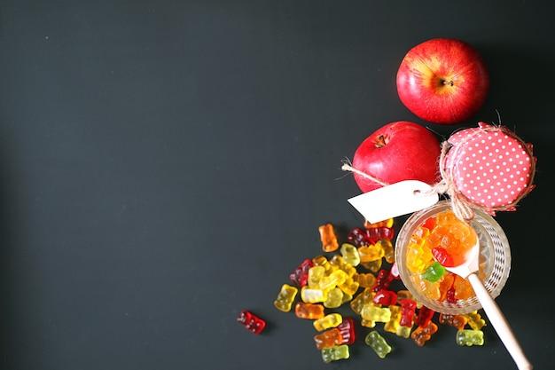 Marmelade in een vaas op tafel. snoepjes in een kom op een zwarte achtergrond. veelkleurige gelei-snoepjes voor kinderen.