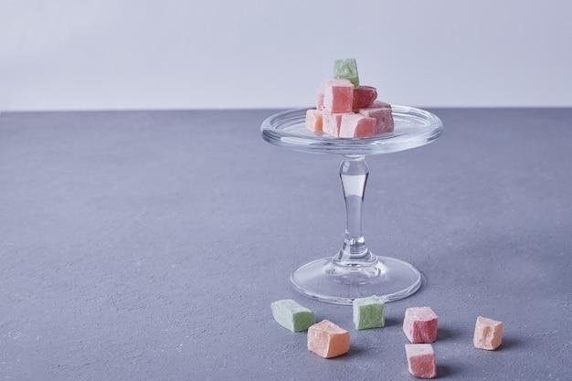 Marmelade snoepjes in een glazen beker op blauw.
