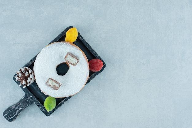 Marmelades, dennenappel en een donut op een zwart dienblad op marmer.
