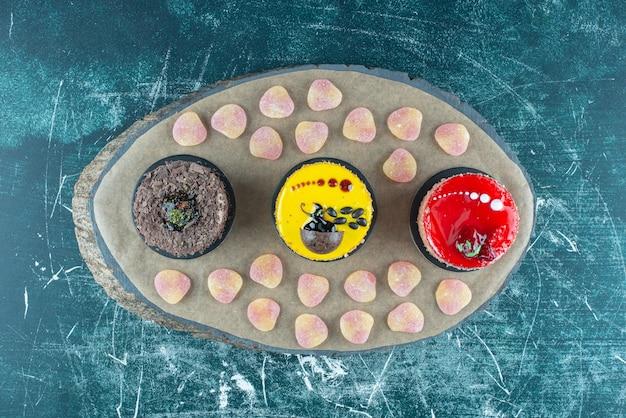 Marmelades en cakes gebundeld op een houten bord op blauw.