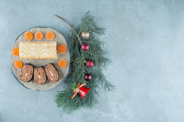 Marmelades en een cakerol met plakjes op een schaal met een versierde dennentak op marmer.