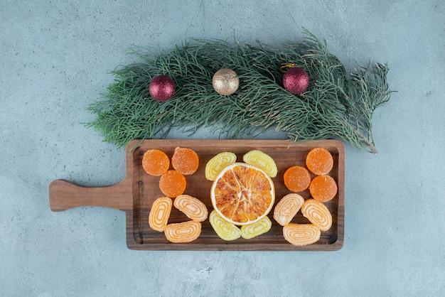 Marmelades en een schijfje gedroogde sinaasappel op een dienblad naast een kleine slinger op marmer.