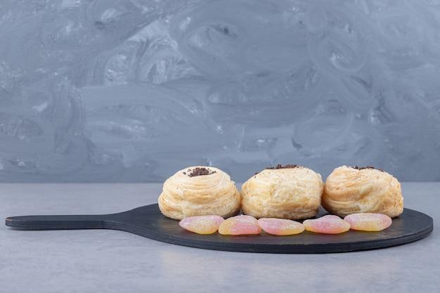 Marmelades en schilferige taarten op een zwart bord op marmeren tafel.