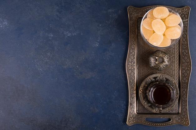 Marmelades met een glas thee in een metalen schaal, bovenaanzicht