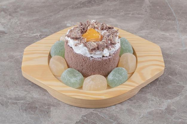 Marmelades rond een kleine cake op een houten schaal op marmer