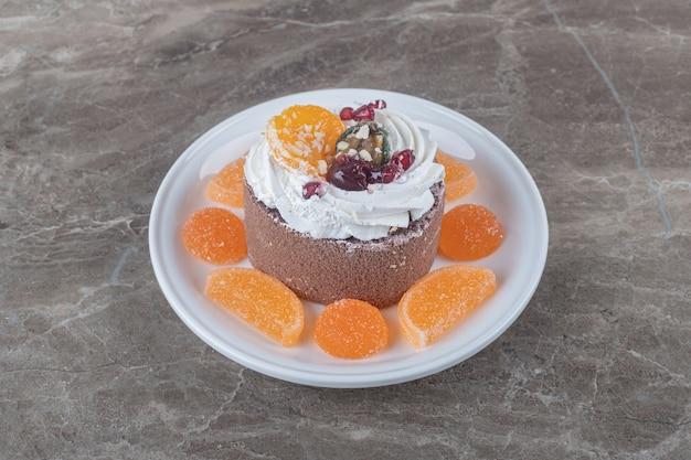 Marmelades rond een kleine cake op een schaal op marmeren ondergrond
