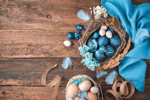 Marmerblauwe paaseieren in een rieten nest met veren en bloemen naast een blauw servet en een