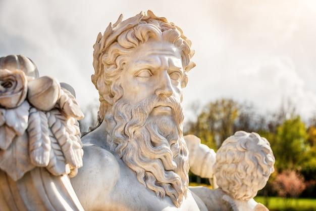 Marmeren beeld van griekse god met hoorn des overvloeds in zijn handen