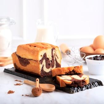 Marmeren chocoladetaart met bakingrediënten, wit bakkerijconcept
