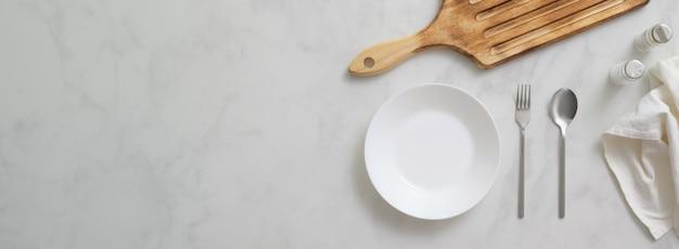 Marmeren eettafel met wit bord, bestek, houten dienblad en kopie ruimte