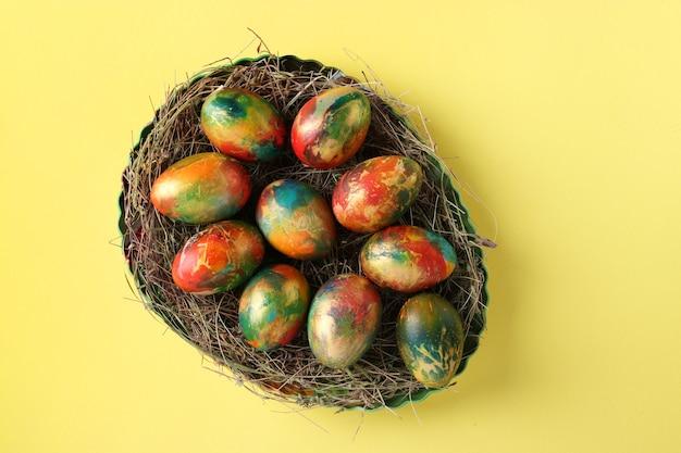 Marmeren eieren beschilderd met voedselkleuren voor pasen op een gele achtergrond.