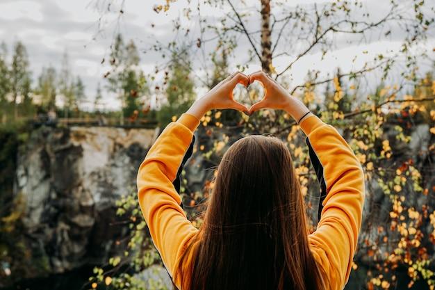 Marmeren kloof in ruskeala, karelië met meisje dat het hart van de hand boven het hoofd laat zien