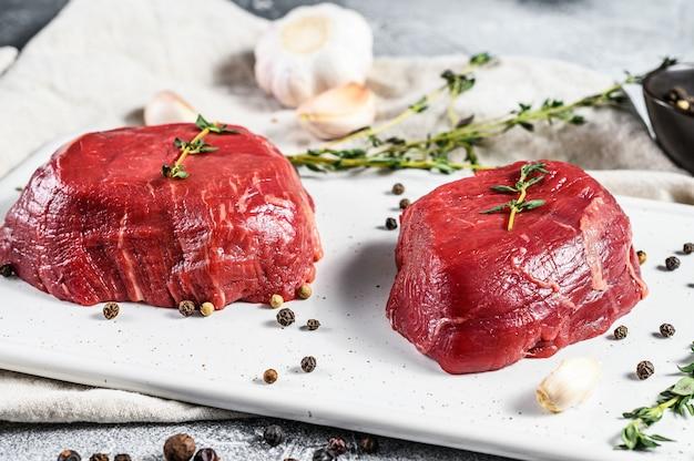 Marmeren ossenhaas. ruwe filet mignon steak op een witte snijplank. grijze muur. bovenaanzicht