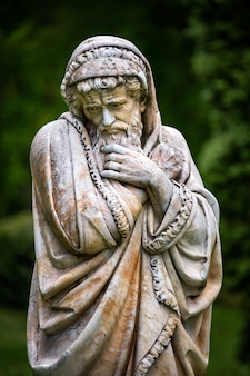Marmeren parkbeeld van een oude man die bevriest en in dekens is gewikkeld die het koude seizoen van het jaar personifiëren