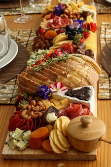 Marmeren snijplank met gorgonzolamousse, brie, brood, chocolade, jam, druiven, fruit, noten, eetbare bloemen, salame, etc.