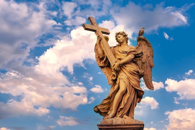 Marmeren standbeeld van engel met het kruis bij zonsondergang, een van de tien engelen op saint angel bridge, symbolen van de passie van christus, rome, italië