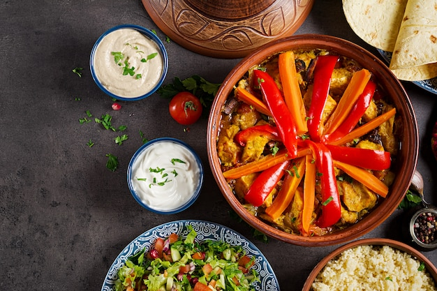 Marokkaans eten. traditionele tajine gerechten, couscous en verse salade op rustieke houten tafel. tajine kippenvlees en groenten. arabische keuken. bovenaanzicht plat leggen