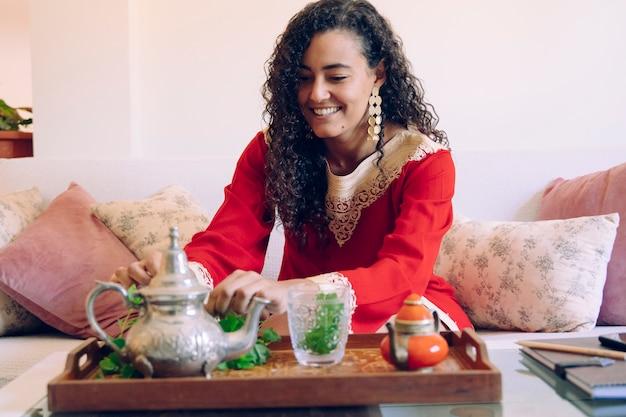 Marokkaans wijfje dat traditionele arabische thee thuis voorbereidt. arabische cultuur en tradities. moslim levensstijl thuis. arabische jonge vrouw met etnische kenmerken die een tak van verse groene munt ruiken.