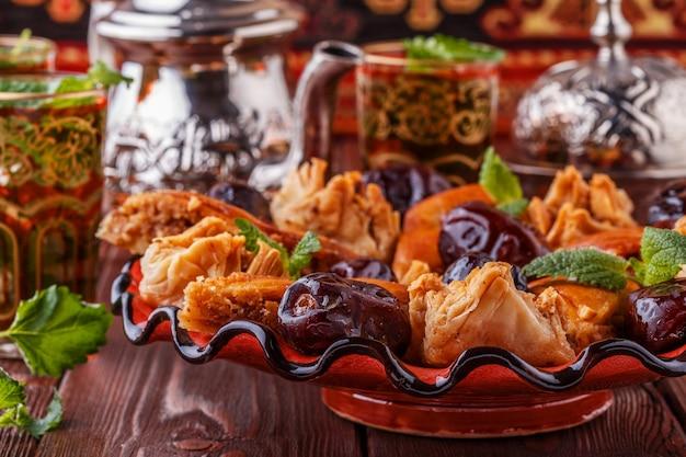 Marokkaanse muntthee in de traditionele glazen met snoep, selectieve focus.
