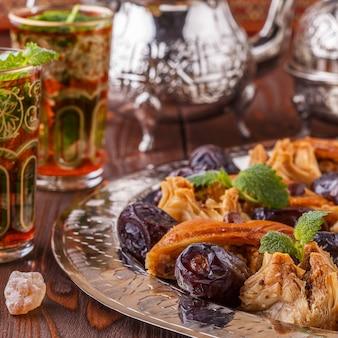 Marokkaanse muntthee in de traditionele glazen met snoepjes