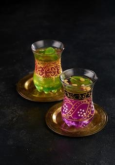 Marokkaanse muntthee in de traditionele glazen op zwarte achtergrond