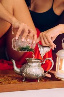 Marokkaanse vrouw die traditionele arabische thee thuis voorbereidt