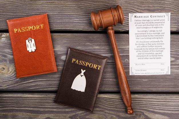 Marriace contract plat gelegd. bovenaanzicht echtpaar paspoorten met hamer.