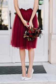 Marsala tule rok, boeket bloemen in handen van slank meisje op straat